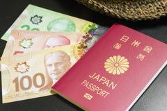 Dólares canadenses e passaporte japonês Fotos de Stock