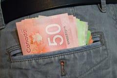 Dólares canadienses en bolsillo de pantalones de la mezclilla imagen de archivo
