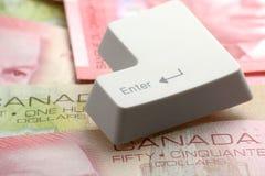 Dólares canadienses y un clave de introducir Fotografía de archivo libre de regalías
