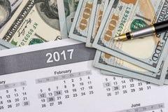 Dólares com a calculadora no calendário Foto de Stock Royalty Free