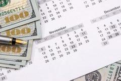 Dólares con la calculadora en el calendario Imagen de archivo libre de regalías