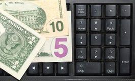 Dólares das cédulas no teclado do portátil Fotografia de Stock