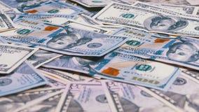 Dólares de cuentas americanos de diversas denominaciones que giran en la tabla almacen de metraje de vídeo