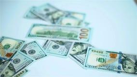 Dólares de EE. UU. de billetes de banco que caen en la superficie blanca Salarios, arnings, ganancias almacen de metraje de vídeo