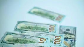 Dólares de EE. UU. de billetes de banco que caen en la superficie blanca Salarios, arnings, ganancias almacen de video