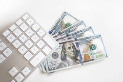 100 dólares de EE. UU. de billetes de banco con el teclado de ordenador Fotografía de archivo libre de regalías