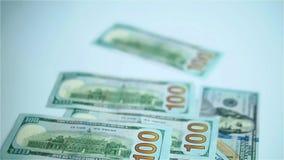 Dólares de EE. UU. de billetes de banco que caen en la superficie blanca Salarios, arnings, ganancias metrajes