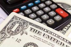Dólares de EE. UU. de billetes de banco que mienten en la superficie de la calculadora electrónica Foco en el billete de banco Foto de archivo libre de regalías