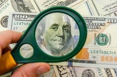 100 dólares de EE. UU. debajo de una lupa Fotografía de archivo