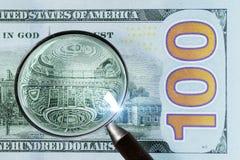 100 dólares de EE. UU. debajo de la lupa Foto de archivo libre de regalías