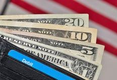Dólares de EE. UU. en cartera con el fondo de la bandera de los E.E.U.U. Foto de archivo libre de regalías
