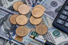 Dólares de EE. UU., moneda, calculadora y pluma fotografía de archivo libre de regalías