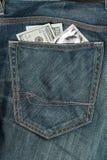Dólares de EE. UU. y condón en el bolsillo de los vaqueros Fotos de archivo libres de regalías