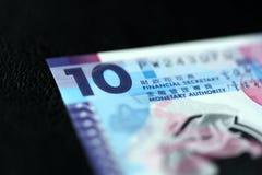10 dólares de Hong Kong em um fundo escuro Fotografia de Stock Royalty Free