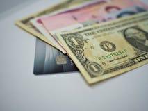 Dólares de kyat y yenes del baht sobre tarjeta de crédito imagen de archivo