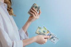 Dólares de la paga en manos femeninas foto de archivo