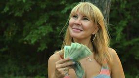 Dólares de ondulação da mulher na frente da cara vídeos de arquivo