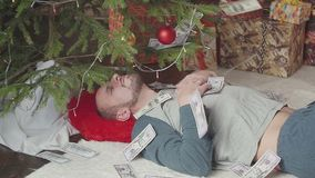 Dólares de queda Um homem está dormindo perto de uma árvore de Natal vídeos de arquivo