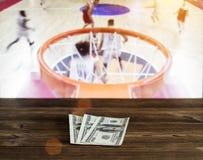 Dólares del dinero en un fondo de madera en el fondo de una TV que muestra baloncesto fotografía de archivo libre de regalías