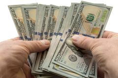 Dólares do dinheiro nas mãos no isolamento branco do fundo imagens de stock royalty free