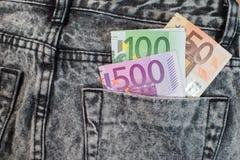 Dólares do Euro no bolso das calças de brim Foto de Stock Royalty Free