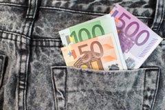 Dólares do Euro no bolso das calças de brim dinheiro europeu Imagens de Stock Royalty Free