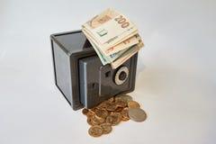 Dólares do metal amarelo e moedas diferentes das contas em seguro cinzento, isolado imagens de stock