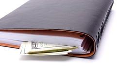 dólares e caderno em um fundo branco Foto de Stock