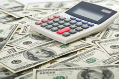 Dólares e calculadora com a tecla vermelha positiva Fotografia de Stock