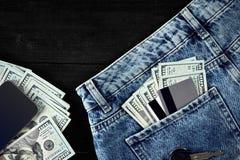 Dólares e cartões em suas calças de brim do bolso, dinheiro, esperto no fundo de madeira preto Foto de Stock Royalty Free
