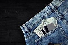 Dólares e cartões em suas calças de brim do bolso no fundo de madeira preto Imagens de Stock