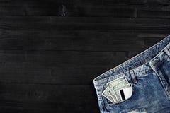 Dólares e cartões em suas calças de brim do bolso no fundo de madeira preto Foto de Stock Royalty Free