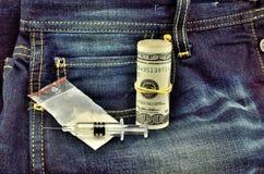 Dólares e seringa brancos do pó em calças de brim Fotos de Stock