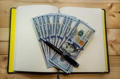 Dólares e uma pena preta em um caderno fotos de stock