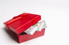 Dólares em uma caixa de presente vermelha em um fundo branco Busca para um presente para o feriado ilustração com curva vermelha  imagem de stock