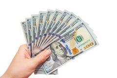 Dólares em uma mão em um fundo branco Imagem de Stock