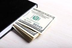 Dólares en cuaderno, cierre para arriba Imagen de archivo libre de regalías