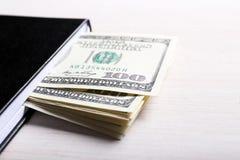 Dólares en cuaderno en fondo de madera ligero Fotos de archivo