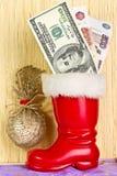 Dólares en la bota de Santa Claus Fotografía de archivo libre de regalías