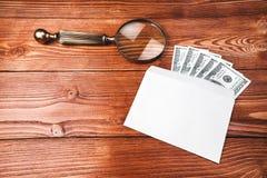 Dólares en un sobre con la lupa Fotografía de archivo libre de regalías