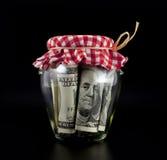 Dólares en un tarro Fotos de archivo libres de regalías