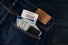 Dólares, esperto, passaporte e bilhete plano em suas calças de brim do bolso no fundo de madeira preto Fotografia de Stock