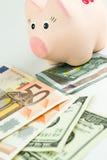 Dólares, Euro e moneybox Imagem de Stock Royalty Free