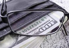 Dólares na carteira preta através dos vidros Fotografia de Stock