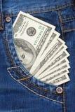 Dólares no bolso das calças de brim Imagens de Stock Royalty Free