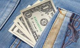 Dólares no bolso das calças de brim Imagem de Stock