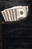 Dólares no bolso das calças de brim Fotos de Stock