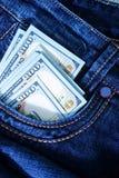 Dólares no bolso das calças de brim Fotografia de Stock