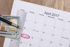 Dólares no calendário - em abril de 2017 com pena Fotos de Stock