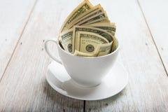 Dólares no copo fotografia de stock royalty free